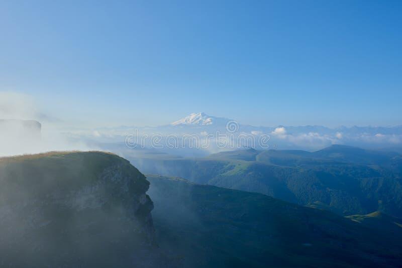Elbrus στην ανατολή, την ομίχλη και τα σύννεφα στο πρώτο πλάνο Γόμμα-Bashi πέρασμα, βόρειος Καύκασος, Ρωσία στοκ φωτογραφίες με δικαίωμα ελεύθερης χρήσης