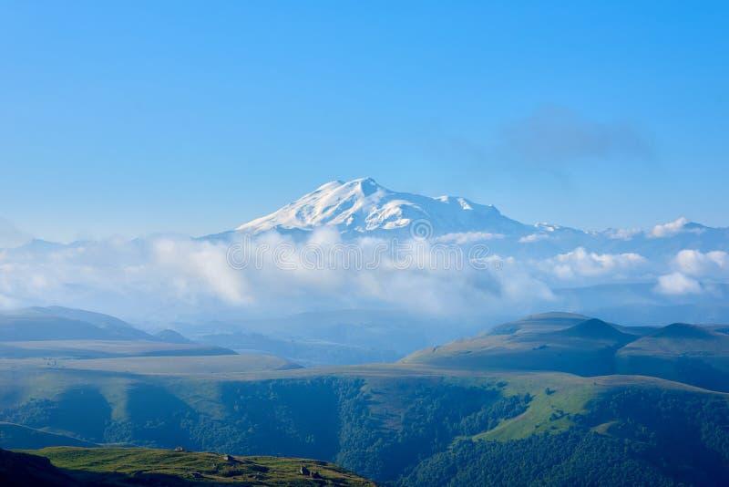 Elbrus στην ανατολή, την ομίχλη και τα σύννεφα στο πρώτο πλάνο Γόμμα-Bashi πέρασμα, βόρειος Καύκασος, Ρωσία στοκ φωτογραφία με δικαίωμα ελεύθερης χρήσης