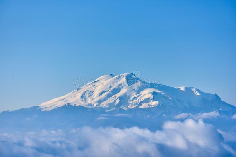 Elbrus στην ανατολή, την ομίχλη και τα σύννεφα στο πρώτο πλάνο Γόμμα-Bashi πέρασμα, βόρειος Καύκασος, Ρωσία στοκ φωτογραφίες