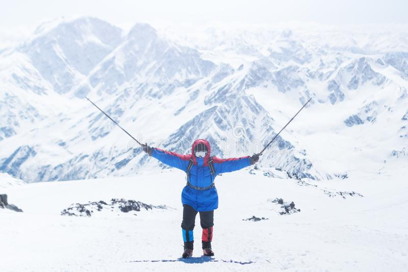 Elbrus, a mountaineer on the ascent, raised the trekking poles up. Russia, Caucasus stock photo