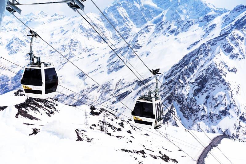 ELBRUS, RÚSSIA - 12 DE ABRIL DE 2018: Teleféricos em um fundo das montanhas na estância de esqui de Elbrus, as montanhas de Cáuca foto de stock