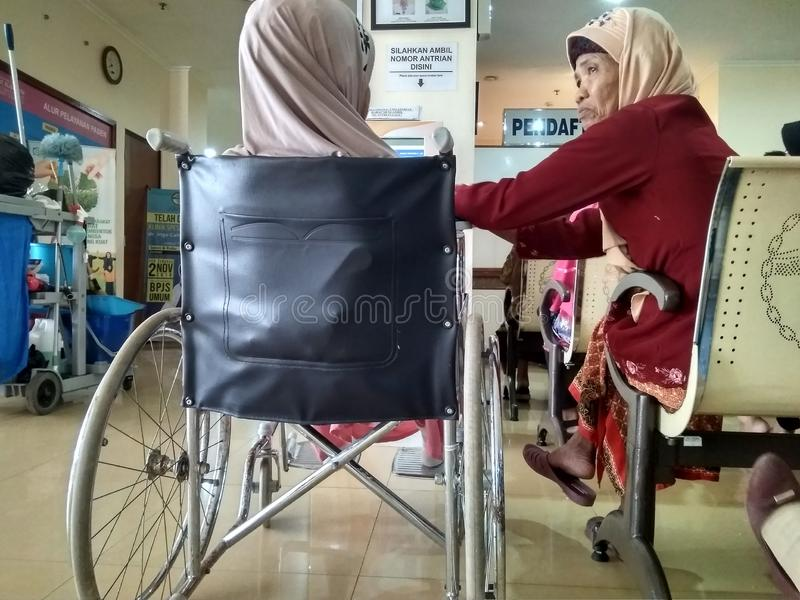 Eldely woman cheering up a fellow patient. An elderly woman is accompanying patient registration in purwokerto indonesia 26 June 2019 royalty free stock images