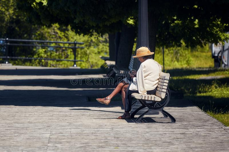 Elder African American woman sits on the wooden bench in a park and browses her smartphone stock photos