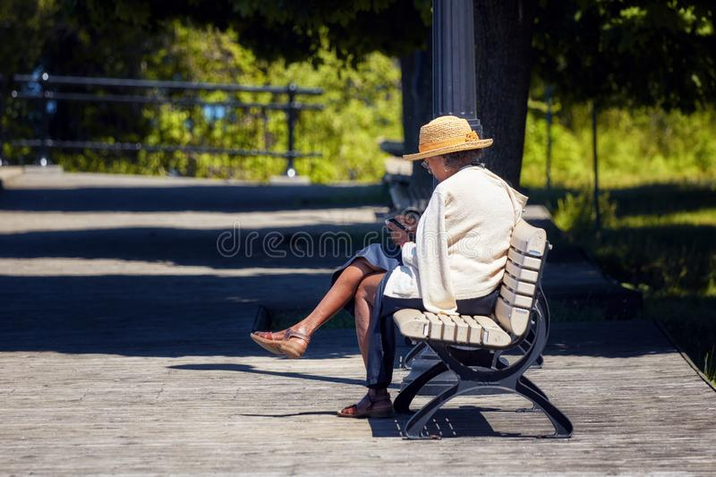 Elder African American woman sits on the wooden bench in a park and browses her smartphone royalty free stock images