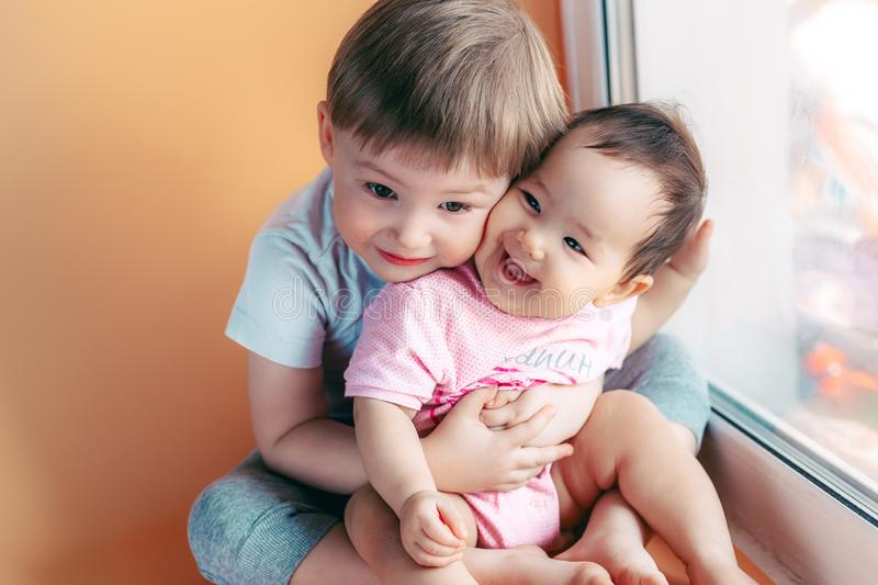 Elder brother hugging his baby sister playing and smiling together. family concept love protect.  stock image