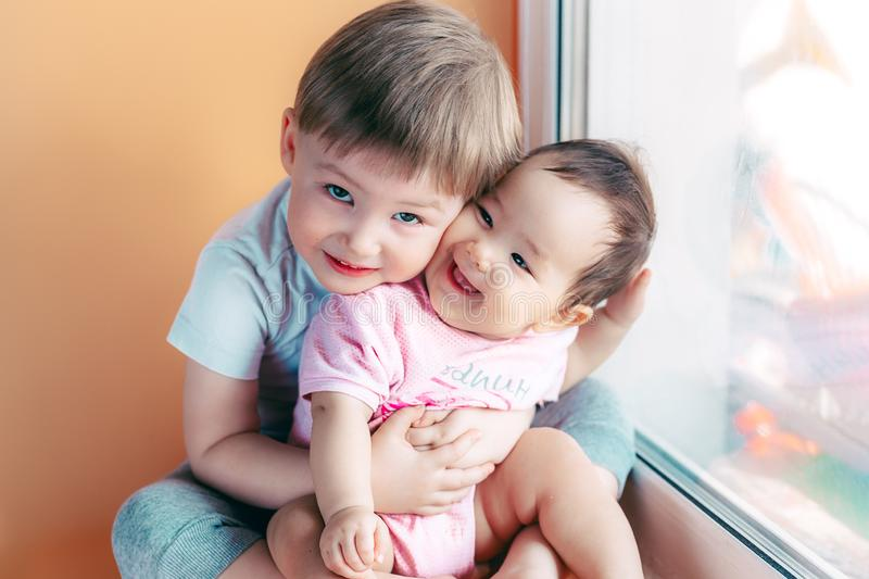 Elder brother hugging his baby sister playing and smiling together. family concept love protect.  royalty free stock photos