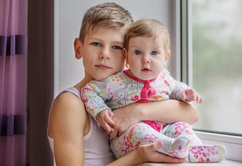 The elder brother hugs his baby sister. At home stock photo
