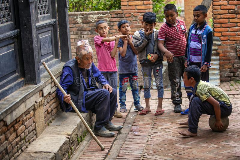 Elder with children, Bhaktapur, Nepal. Elder man sitting on stoop surrounded by young children outside home in Bhaktapur, Nepal royalty free stock photos