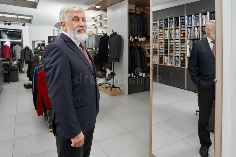 Elder client looking at camera while trying on formal suit royalty free stock photo