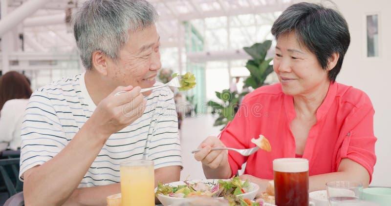 Elder couple eating in restaurant stock images