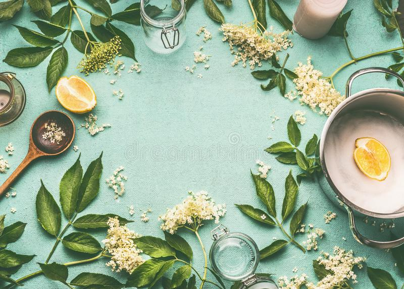 Elder flowers cooking preparation. Frame of Elder flowers with spoon, pot, sugar and lemon on blue table. Background, top view stock images