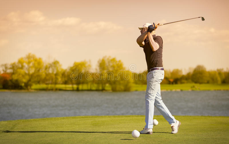 Elder golf player teeing off. Male senior golf player swinging golf club, with lake in background before sunset royalty free stock photos