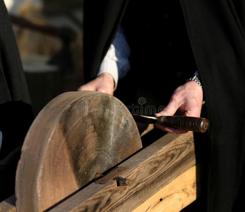 Elder knife sharpener sharpens his knife royalty free stock photography