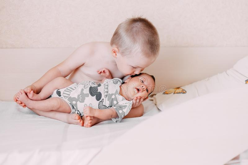elder little blonde toddler brother boy holding his baby sister stock image