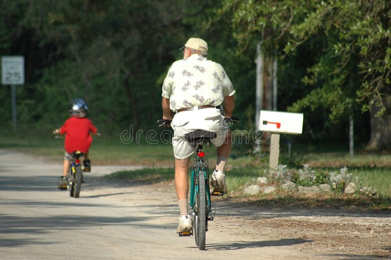 Elder Man And Grandson Bike Riding royalty free stock image
