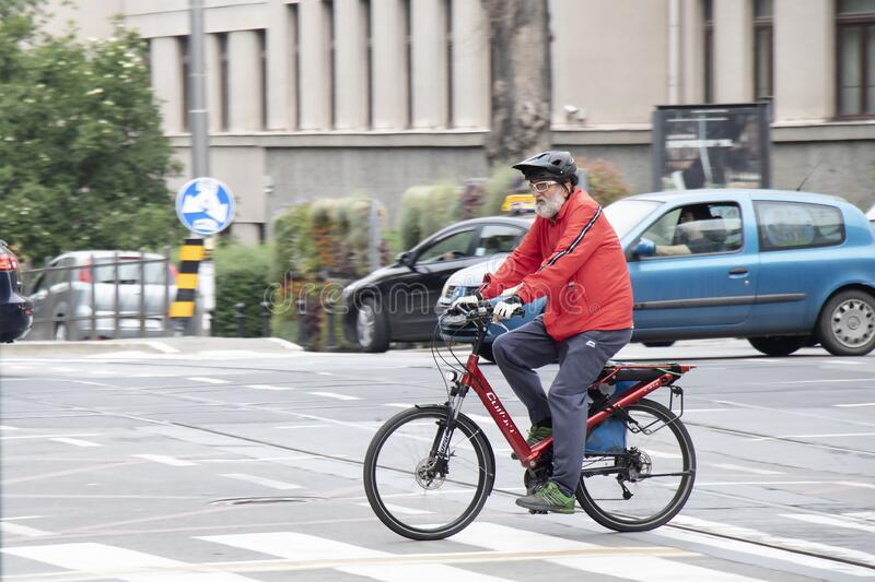 Elder man with gray beard riding a bike in city street traffic royalty free stock image