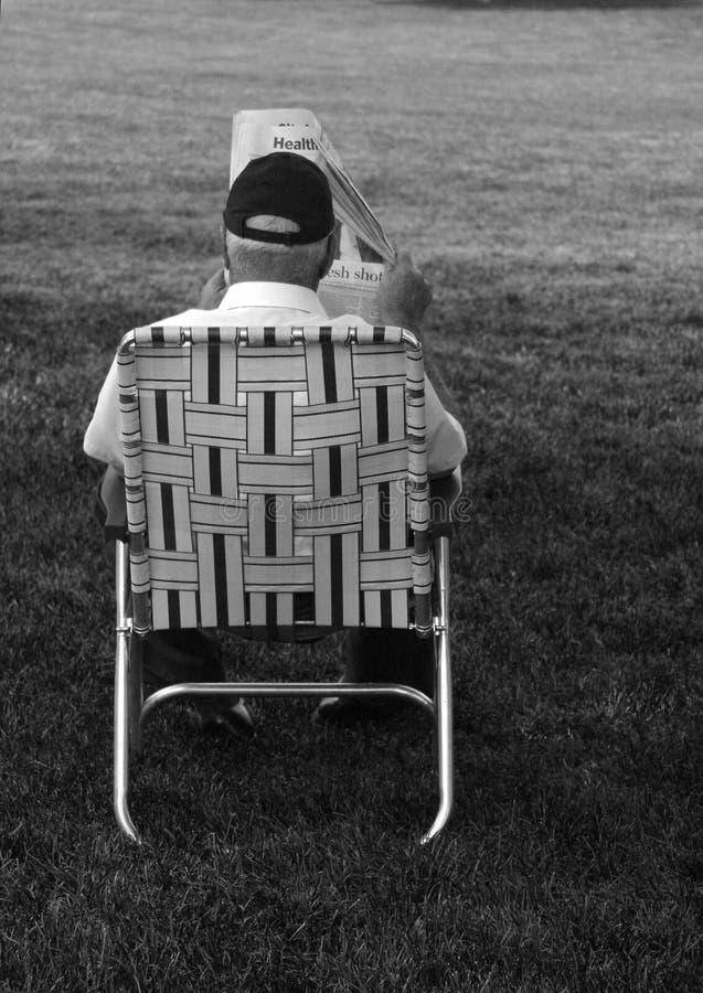 An elder man reading newspaper stock images