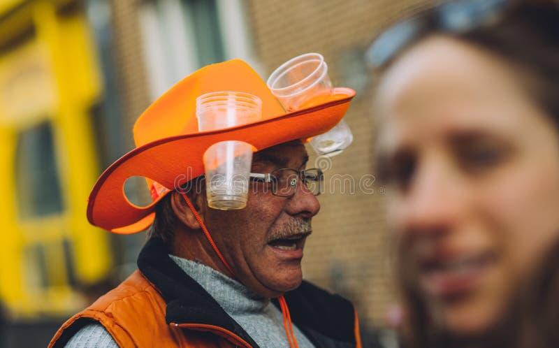 Elder man wearing funny orange beer hat, King`s Day festivity royalty free stock photos
