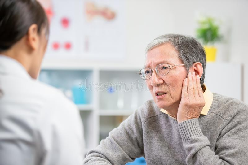 Elder patient feel earaches. Elder patient see an ent doctor and complain about earaches stock image