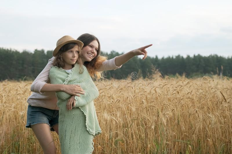 Elder sister hugged younger and shows a hand to the side stock image