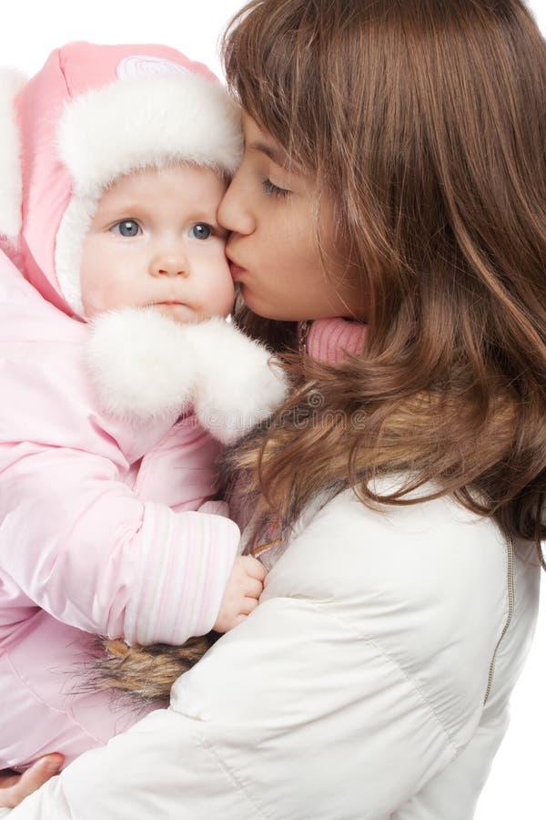 Elder sister kissing baby girl stock photo