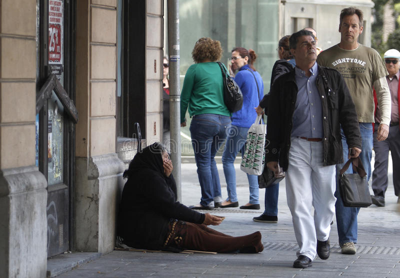 Elder woman begging downtown. A woman begs for money on a commercial street in Palma de Mallorca on the Spanish Balearic island, October 9, 2012. The IMF said stock photo