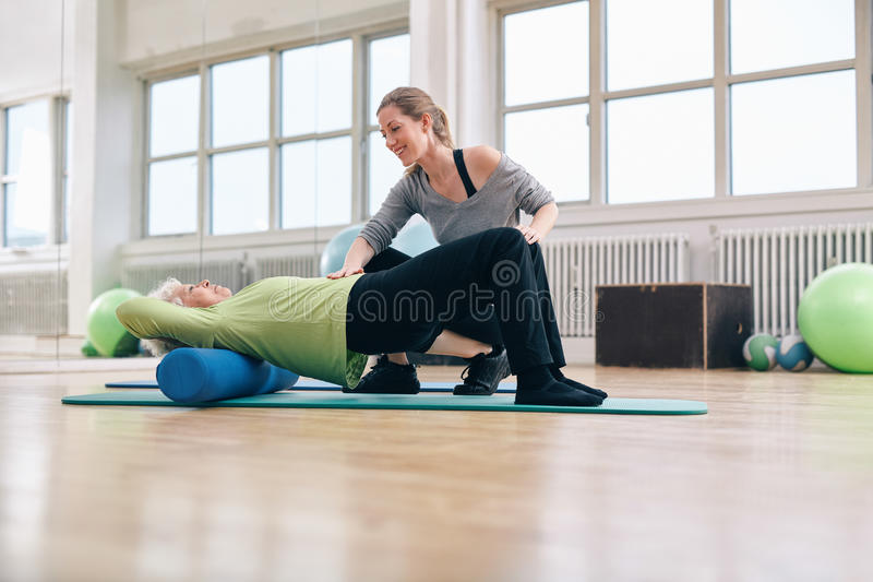 Elder woman doing pilates workout with personal instructor stock photo