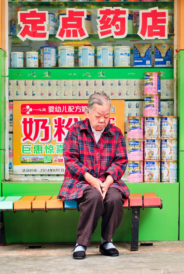 Elder woman having a nap in front of farmacy shop, Kunming, China stock photos