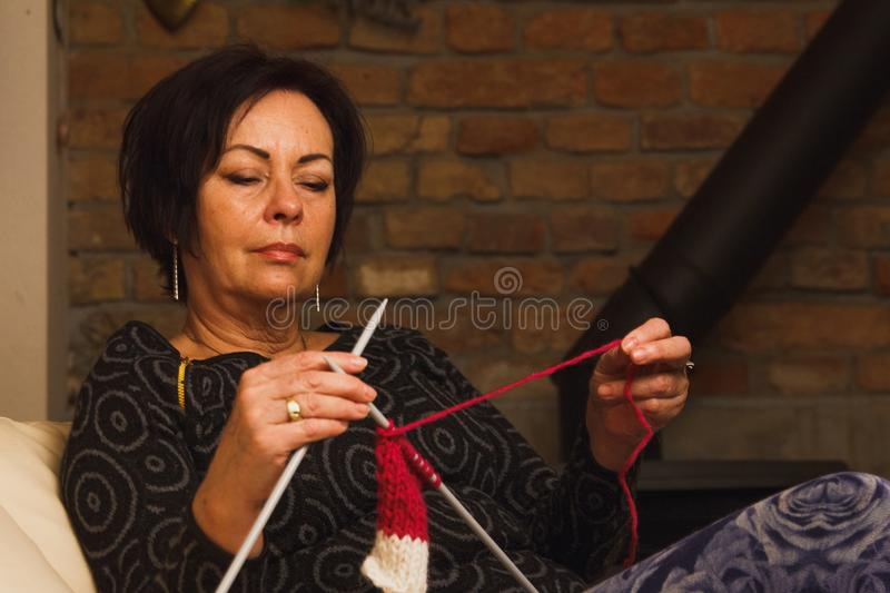 Elder woman knitting on a couch. Pics show elder woman knitting in her house. She seats comfortably and makes a present for a grandchild royalty free stock images