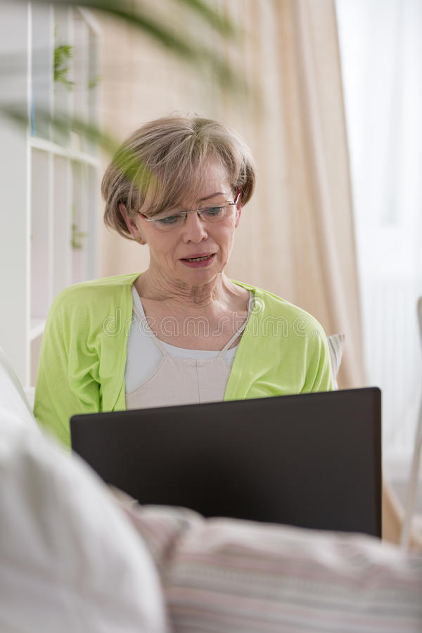 Elder woman with laptop stock images
