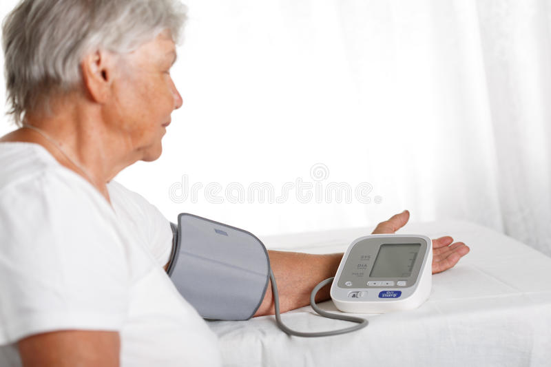 Elder woman measuring blood pressure with automatic manometer at. Home. Self health control, diagnosing and healthcare concept. Long and healthy life or medical stock image