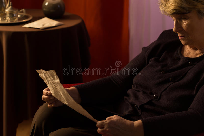 Elder woman reading a letter royalty free stock photography