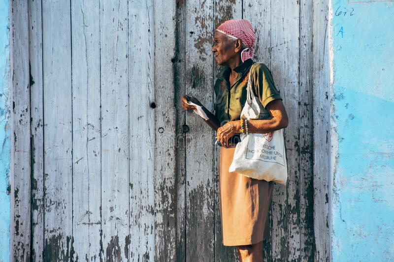 A elder woman rests on the side of the street in Havana, Cuba. A elder woman rests on the side of the street in the evening sun in Havana, Cuba royalty free stock photo