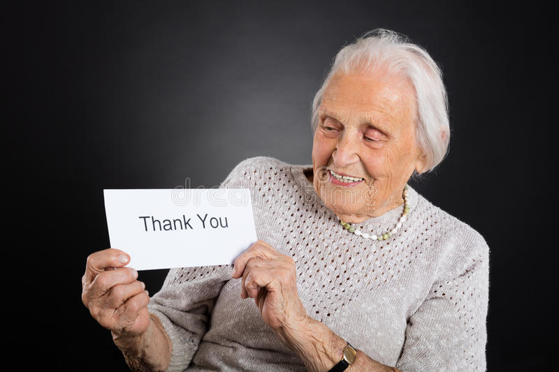 Elder Woman Showing Thank You Card. Portrait Of Smiling Elder Woman Showing Thank You Card Over Grey Background royalty free stock images