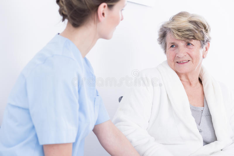 Elder woman talking with her female caregiver. Elder women in bathrobe talking with her female caregiver stock image