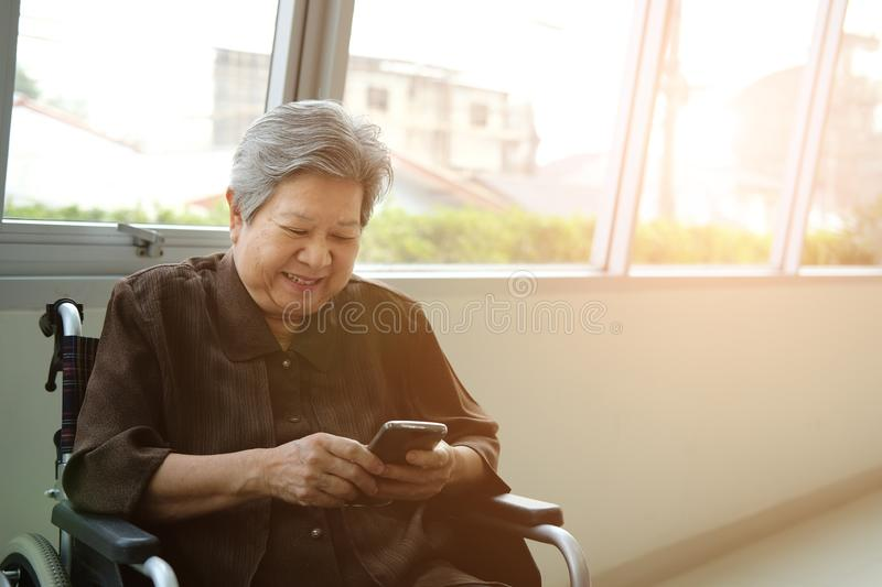 elder woman in wheelchair holding mobile phone. elderly senior using smartphone royalty free stock images