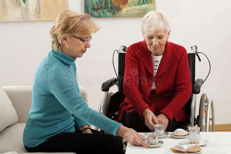 Elder women conversation. Elder women on wheelchair has a nice friend visit for coffee and cake royalty free stock images