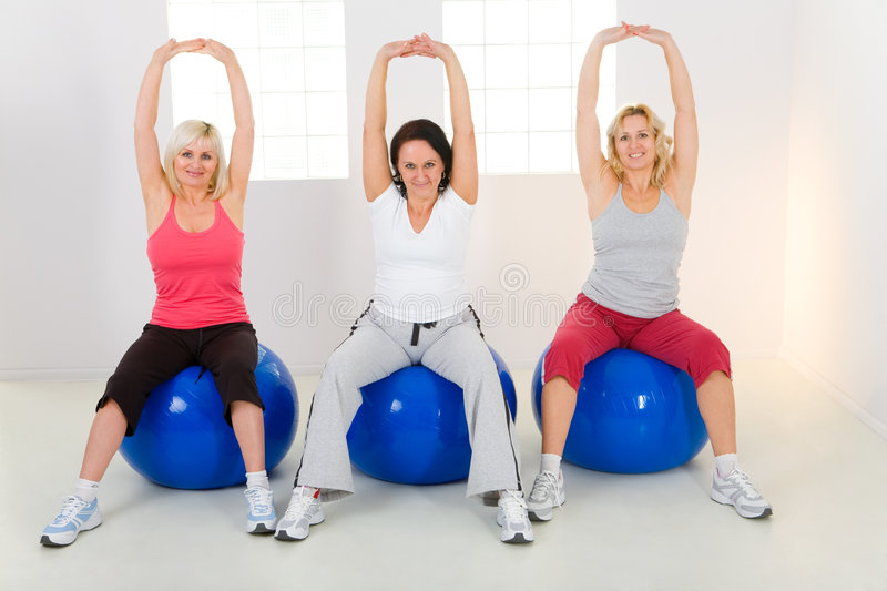 Elder women exercising on fitness balls. Women dresset sportswear working out on fitness ball. They have raised hands. They're smiling and looking at camera stock image