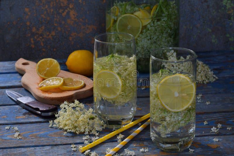 Elderberry flowers and lemon drink. Refreshment healthy elder juice. Glass of elderflower lemonade on wooden rustic board. Alterna stock photos