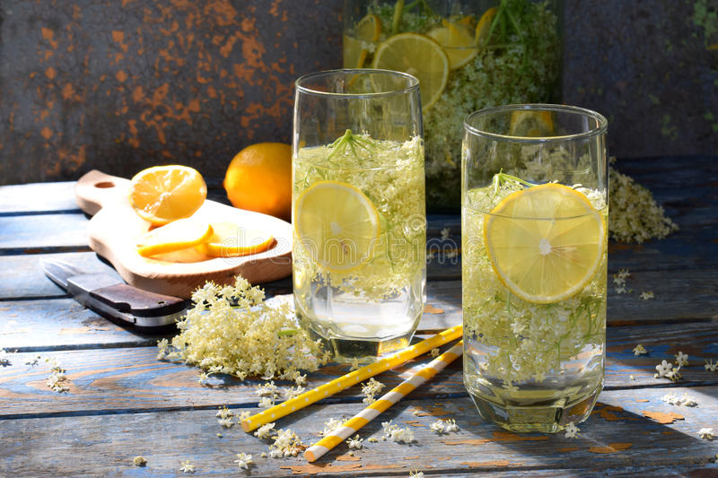 Elderberry flowers and lemon drink. Refreshment healthy elder juice. Glass of elderflower lemonade on wooden rustic board. Alterna. Tive medicine and therapy stock photo