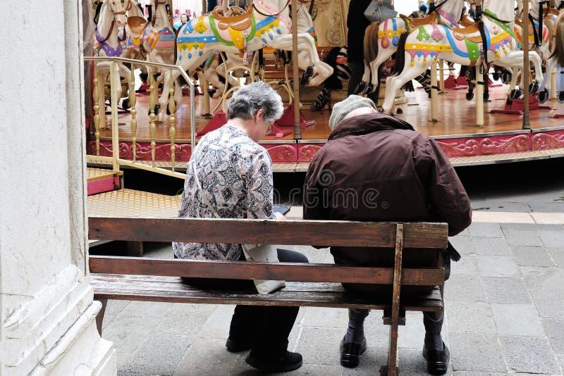 Elderely par som vilar på bänk framme av glat, går rundan i Treviso, Italien royaltyfria foton