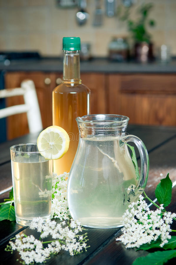 Elderflower juice. Tasty elderflower juice and syrup on kitchen table royalty free stock photo