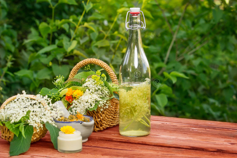 Elderflower juice, medicinal herbs. On garden table royalty free stock images