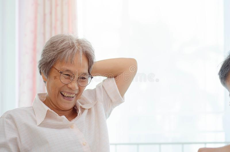 Elderly activities. Asian elderly woman Wearing a blue shirt And friend are playing games Have fun in the morning at home in the room stock image
