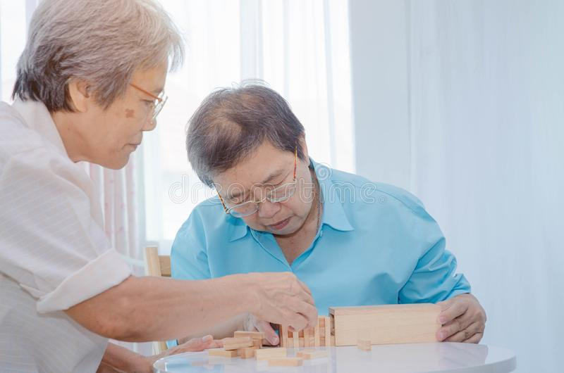 Elderly activities. Asian elderly women Wearing a blue shirt And friend are playing games Have fun in the morning at home in the room royalty free stock photo