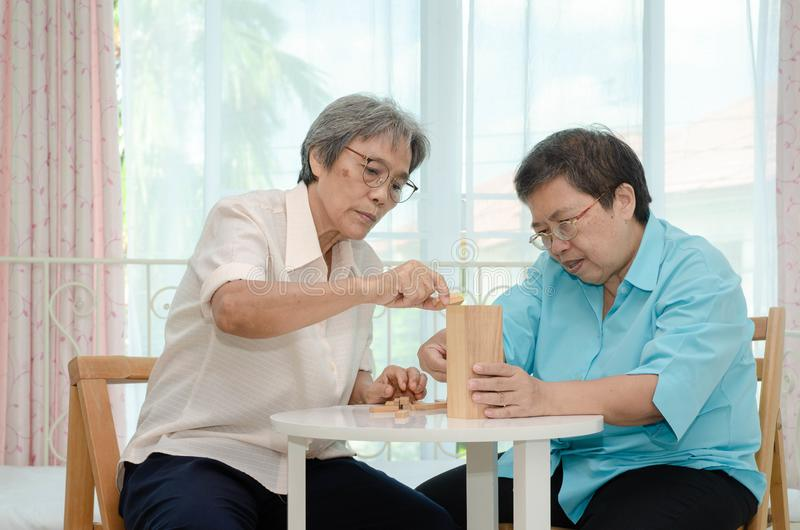 Elderly activities. Asian elderly women Wearing a blue shirt And friend are playing games Have fun in the morning at home in the room royalty free stock images