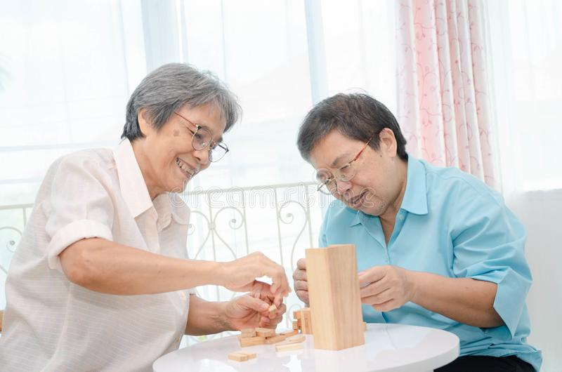 Elderly activities. Asian elderly women Wearing a blue shirt And friend are playing games Have fun in the morning at home in the room stock photography