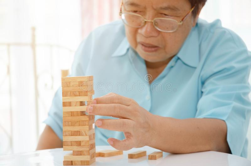 Elderly activities. Asian elderly woman Wearing a blue shirt And friend are playing games Have fun in the morning at home in the room royalty free stock photos