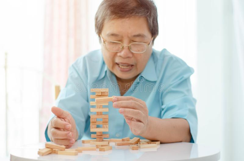 Elderly activities. Asian elderly woman Wearing a blue shirt And friend are playing games Have fun in the morning at home in the room royalty free stock photography