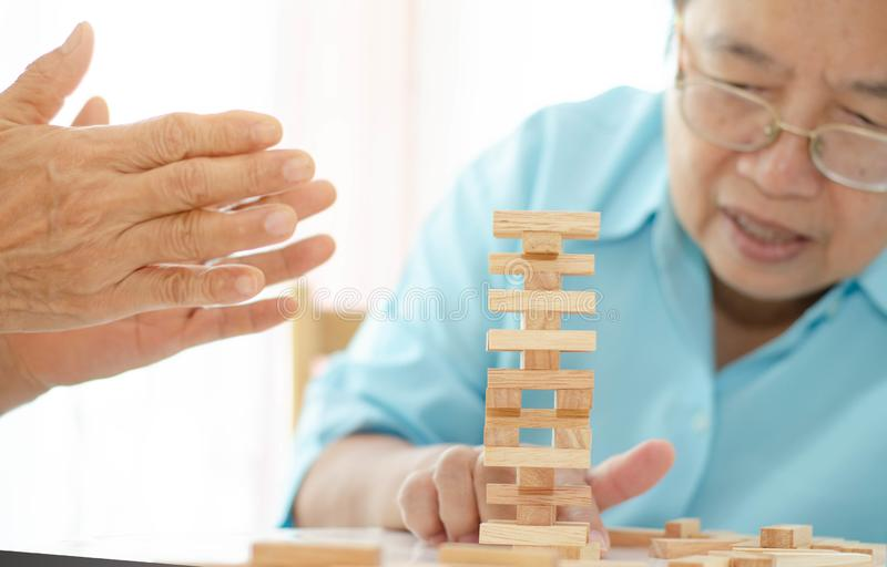Elderly activities. Asian elderly woman Wearing a blue shirt And friend are playing games Have fun in the morning at home in the room stock photo